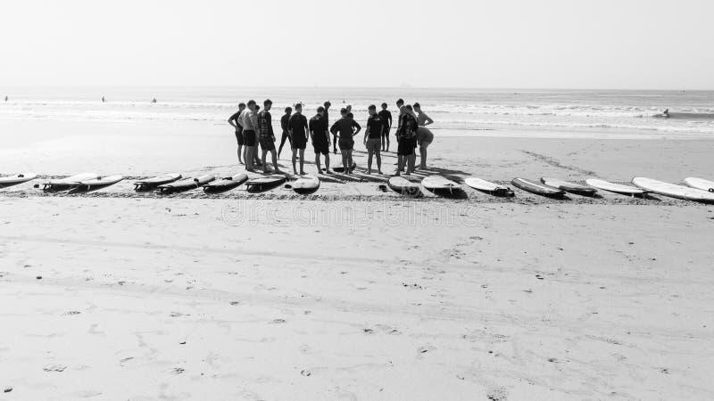 Gli studenti praticanti il surfing di lezioni tirano l'oceano in secco immagini stock libere da diritti