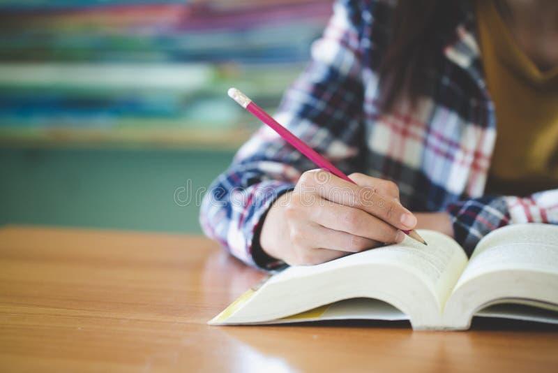 Gli studenti scrivono i libri nella biblioteca, concetto di istruzione immagine stock