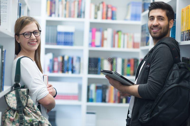 Gli studenti si accoppiano nella biblioteca di scuola fotografia stock libera da diritti