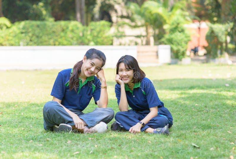 Gli studenti svegli felici sorridono e sedendosi sull'erba fotografia stock