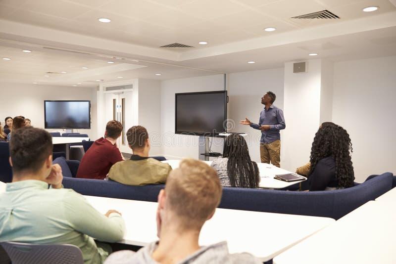 Gli studenti universitari studiano in un'aula con il conferenziere maschio fotografie stock