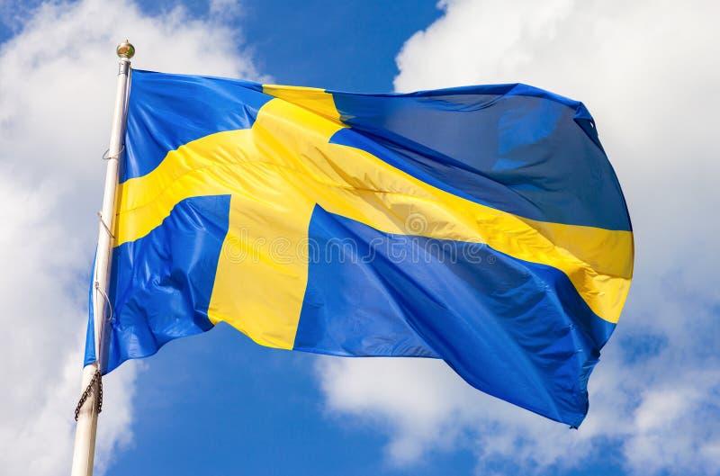 Gli svedese inbandierano il blu con l'incrocio giallo che ondeggia nel vento immagine stock libera da diritti