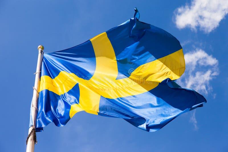 Gli svedese inbandierano l'ondeggiamento nel vento su un cielo blu immagini stock libere da diritti