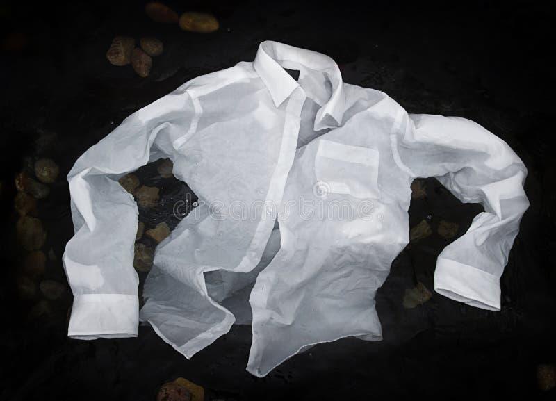 Gli uomini abbottonano la camicia che galleggia o che affonda in acqua fotografie stock libere da diritti
