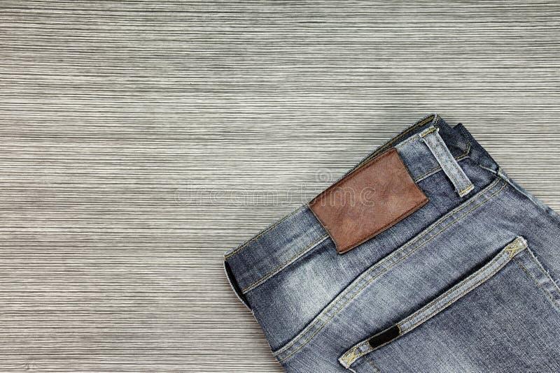 Gli uomini adattano, blue jeans su un fondo di legno marrone fotografia stock libera da diritti