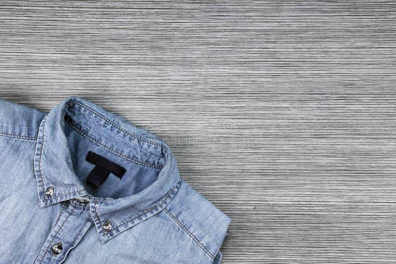 Gli uomini adattano, camicia delle blue jeans su un fondo di legno marrone immagine stock