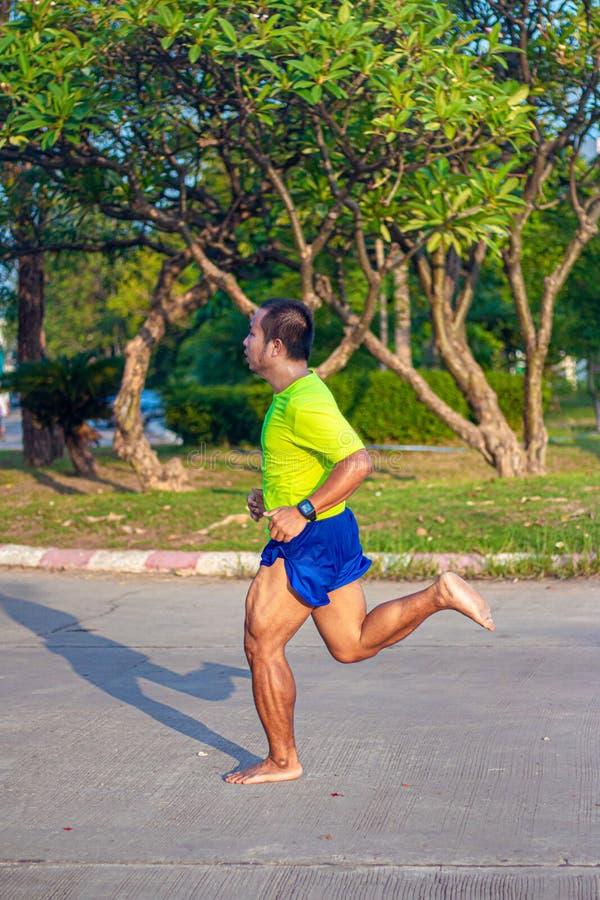 Gli uomini asiatici stanno eseguendo a piedi nudi forte con un pacco potente del muscolo della gamba fa correre naturalmente fotografia stock libera da diritti