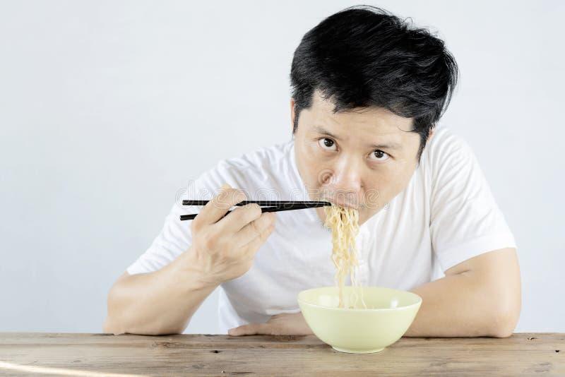 Gli uomini asiatici stanno mangiando le tagliatelle istantanee con deliciousness fotografie stock