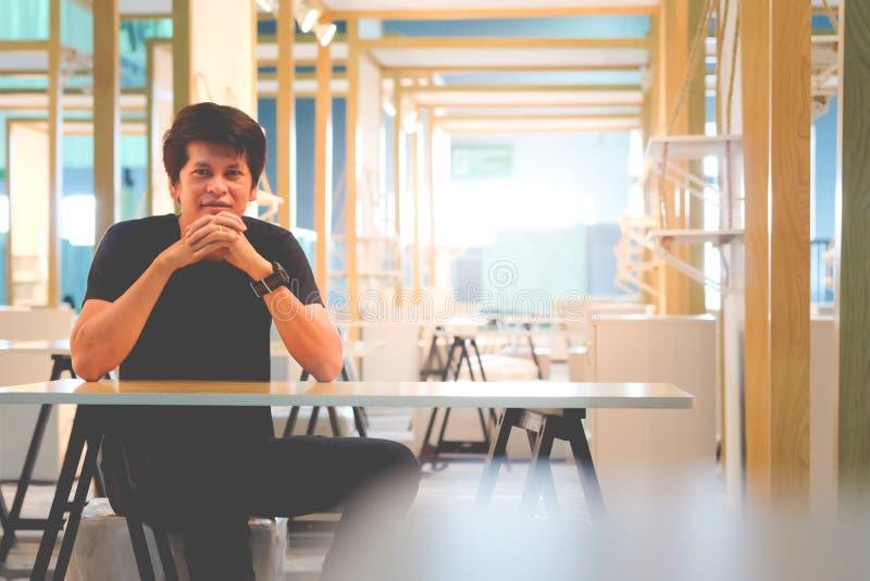 Gli uomini asiatici stanno sedendo pensando qualcosa fotografia stock libera da diritti