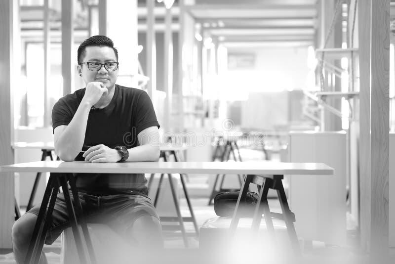 Gli uomini asiatici stanno sedendo pensando qualcosa immagine stock