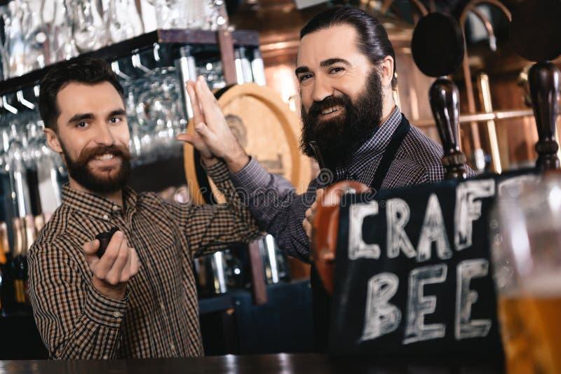 Gli uomini barbuti allegri danno l'un l'altro cinque, tubi di fumo in fabbrica di birra della birra del mestiere fotografie stock libere da diritti