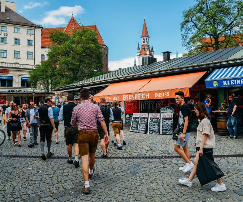 Gli uomini bavaresi tradizionalmente vestiti ad una birra dell'aria aperta fanno il giardinaggio in Viktualienmarkt nel centro st fotografia stock