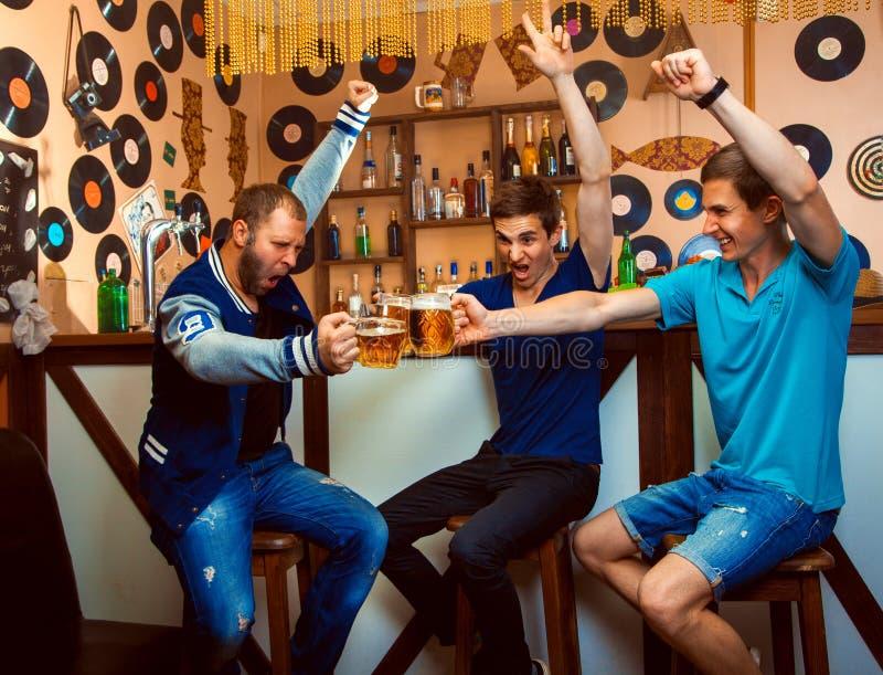 Gli uomini celebrano nei vetri del tintinnio e della barra con la birra fotografia stock