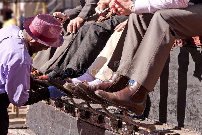 Gli uomini che ottengono una scarpa splendono in città del centro fotografia stock