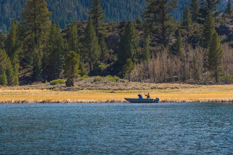 Gli uomini che pescano sulla barca nel lago puntellano fotografia stock