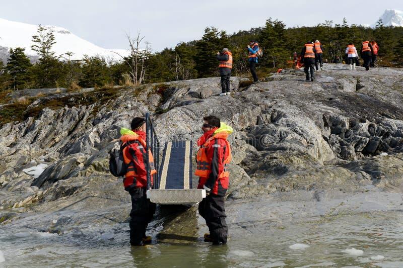 Gli uomini che tengono la scala per lo sbarco dei turisti dalla nave da crociera - a - riva vicino al ghiacciaio del Pia immagine stock