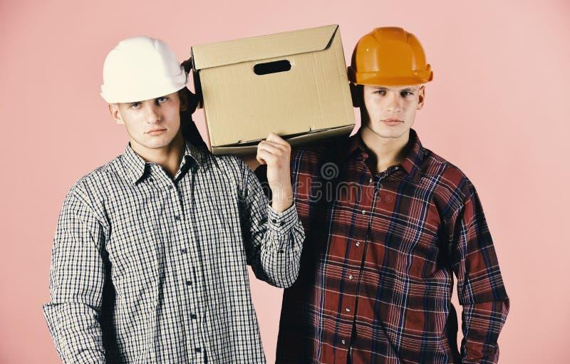 Gli uomini con i fronti scontrosi tengono la scatola di cartone su fondo rosa Consegna, magazzino e concetto d'imballaggio Fratel immagini stock libere da diritti