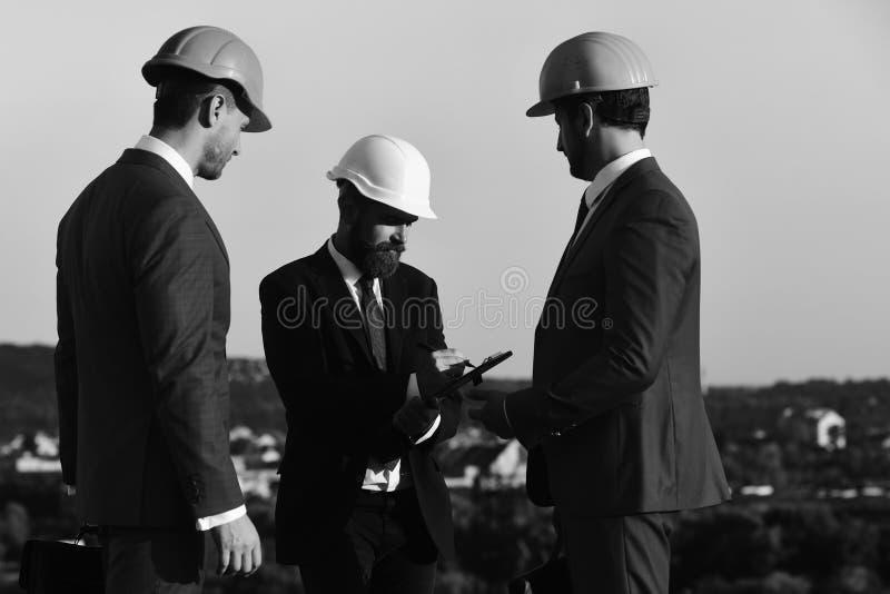 Gli uomini con la barba ed i fronti concentrati fanno le note Cartella e penna della clip della tenuta dei capi Bordo degli archi fotografia stock