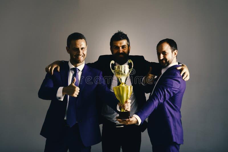 Gli uomini con la barba ed i fronti felici celebrano la vittoria e la direzione Gli uomini d'affari indossano i vestiti ed i lega fotografia stock