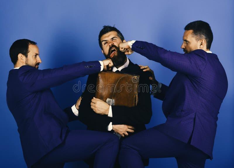 Gli uomini con la barba ed i fronti seri perforano l'uomo con la cartella immagini stock libere da diritti