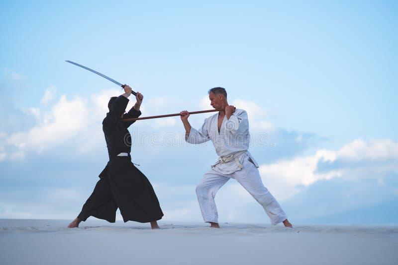 Gli uomini concentrati, in vestiti giapponesi, stanno praticando le arti marziali immagine stock libera da diritti