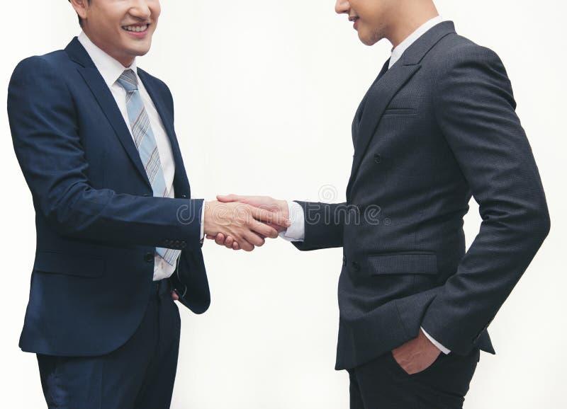 Gli uomini d'affari che emettono un'etichetta commerciale per la stretta di mano su White fotografia stock