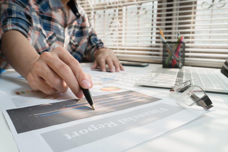 Gli uomini d'affari che lavorano con i dati del grafico all'ufficio, responsabili di finanza incaricano, affare di concetto ed in fotografia stock