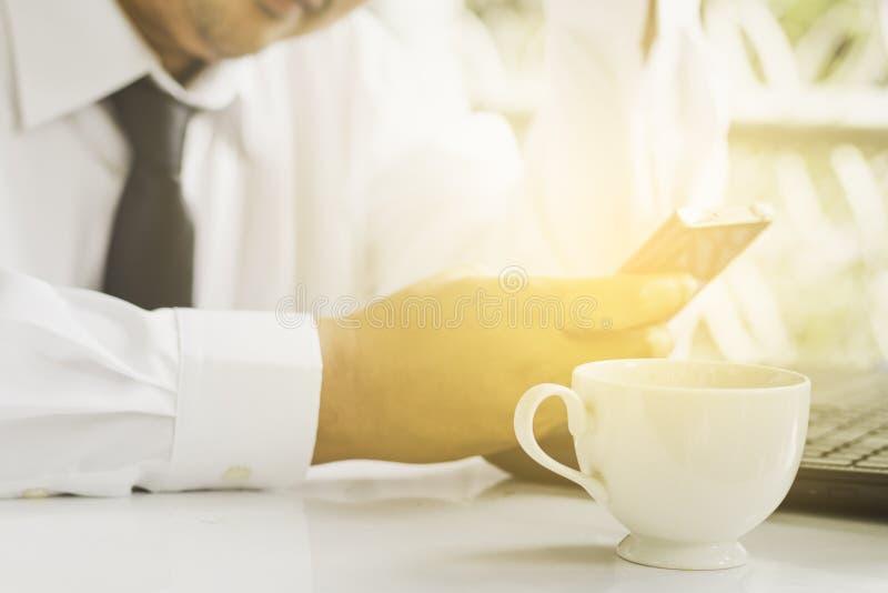 Gli uomini d'affari che sono determinati per lavorare, stanno aggiornando le notizie del telefono cellulare di mattina fotografia stock libera da diritti