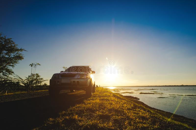 Gli uomini d'affari con le automobili di SUV hanno parcheggiato sulla strada lungo il bacino idrico Sorveglianza del tramonto fotografia stock libera da diritti