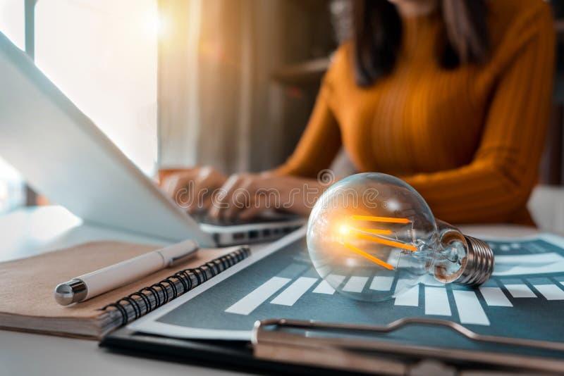 Gli uomini d'affari femminili che utilizzano un computer portatile ed avere una lampadina hanno messo il concetto con innovazione fotografie stock
