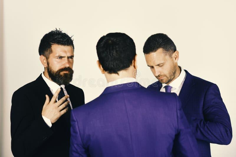 Gli uomini d'affari indossano i vestiti ed i legami astuti Discussione e concetto di affari Uomini con la barba ed i fronti dubbi immagine stock libera da diritti