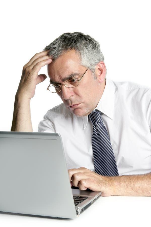 Gli uomini d'affari maggiori hanno messo a fuoco sul lavoro del computer portatile fotografie stock libere da diritti