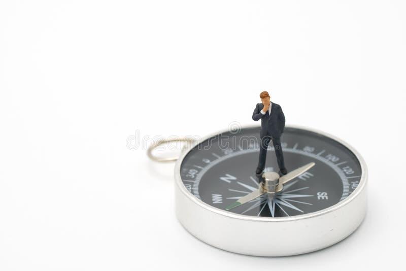 Gli uomini d'affari miniatura della gente analizzano la condizione sulla bussola come il concetto di strategia del fondo e concet immagine stock