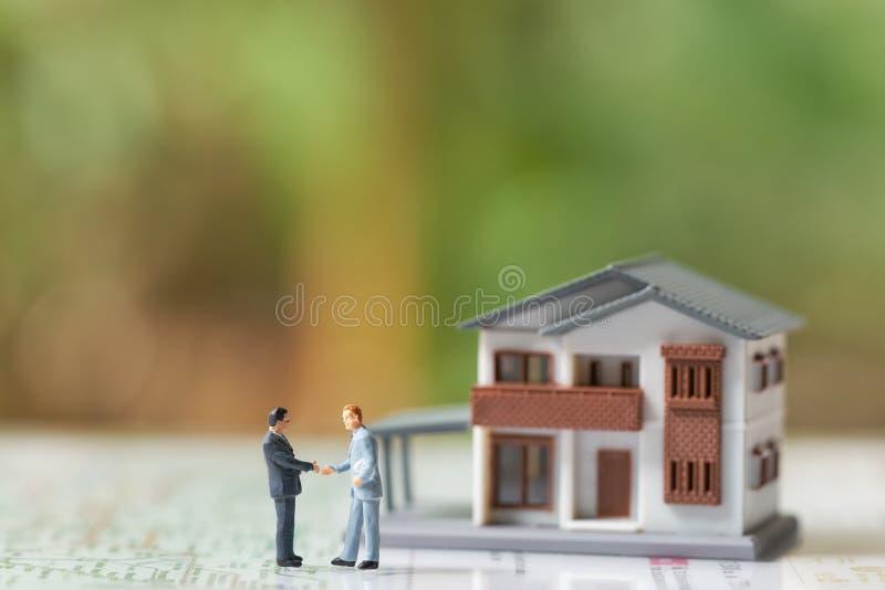 Gli uomini d'affari miniatura di 2 persone stringono le mani con il modello della casa del modello di A come il concetto di affar fotografia stock