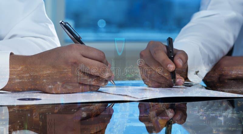 Gli uomini d'affari passa i documenti di firma sullo scape della città dell'orizzonte di Riyad fotografia stock