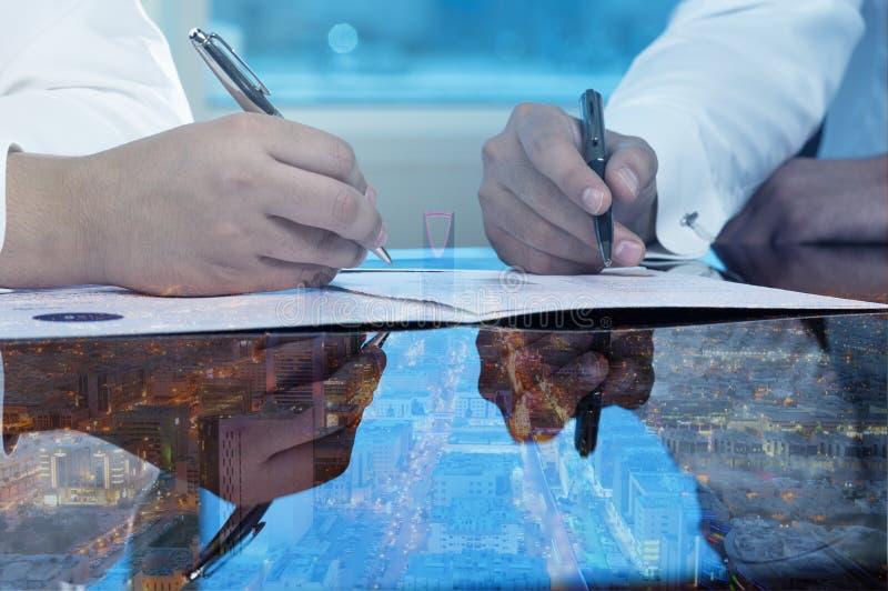 Gli uomini d'affari passa i documenti di firma sullo scape della città dell'orizzonte di Riyad immagine stock