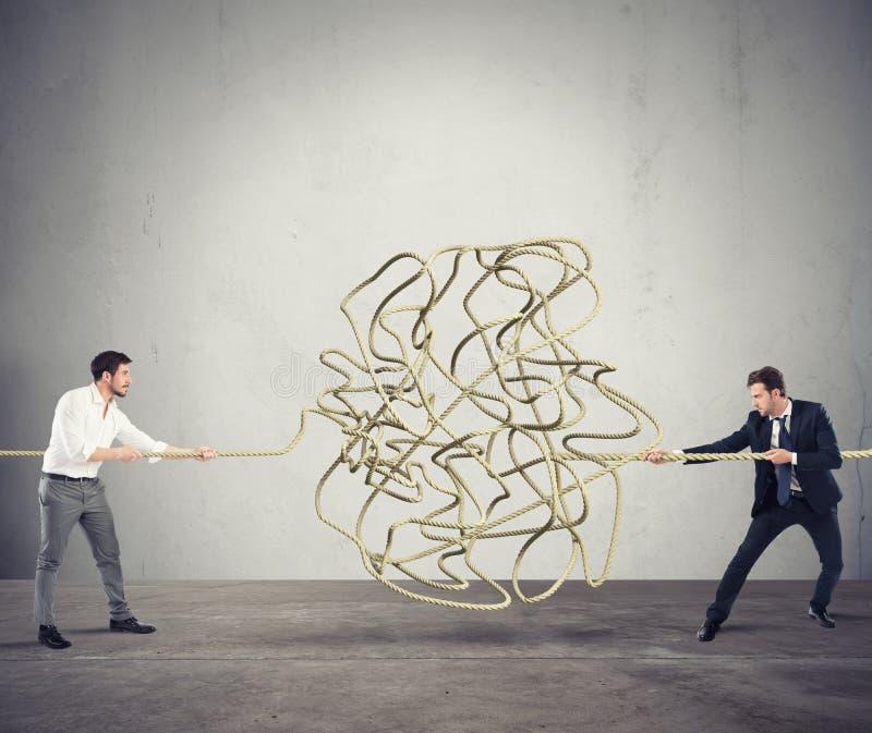 Gli uomini d'affari provano a risolvere una corda aggrovigliata Concetto dell'associazione immagine stock