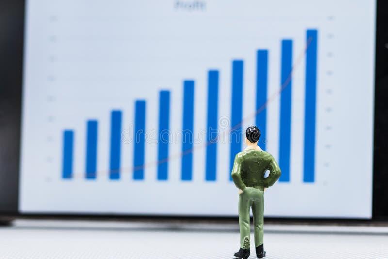 Gli uomini d'affari stanno ed esaminano l'esposizione della crescita di vendita del grafico fotografia stock
