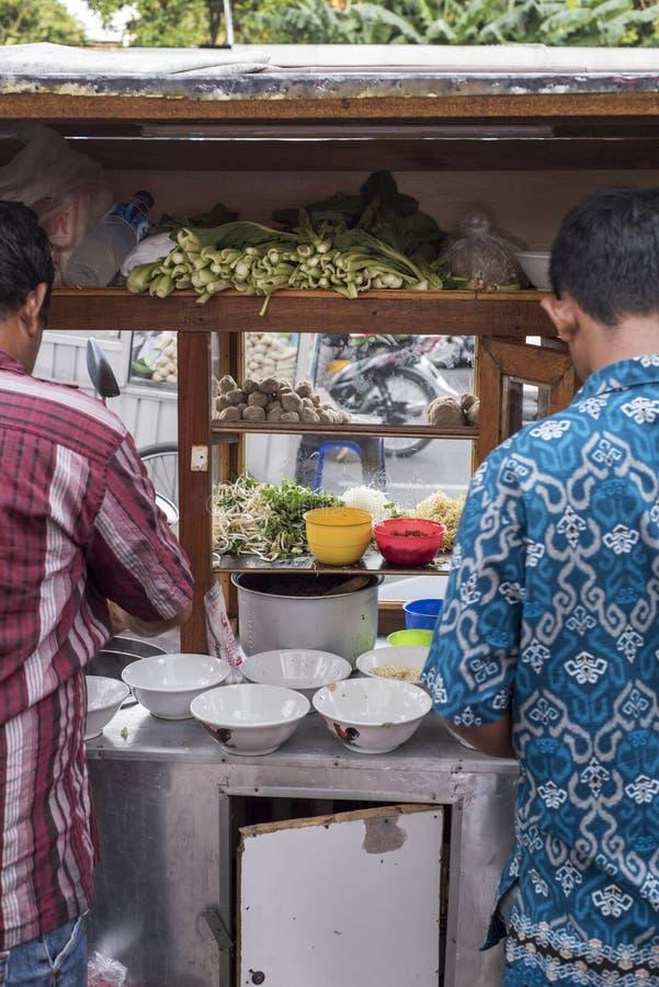 Gli uomini dell'Indonesia preparano l'alimento ad un carretto di legno d'annata di spinta dell'alimento della via a Jakarta, Indo immagine stock libera da diritti