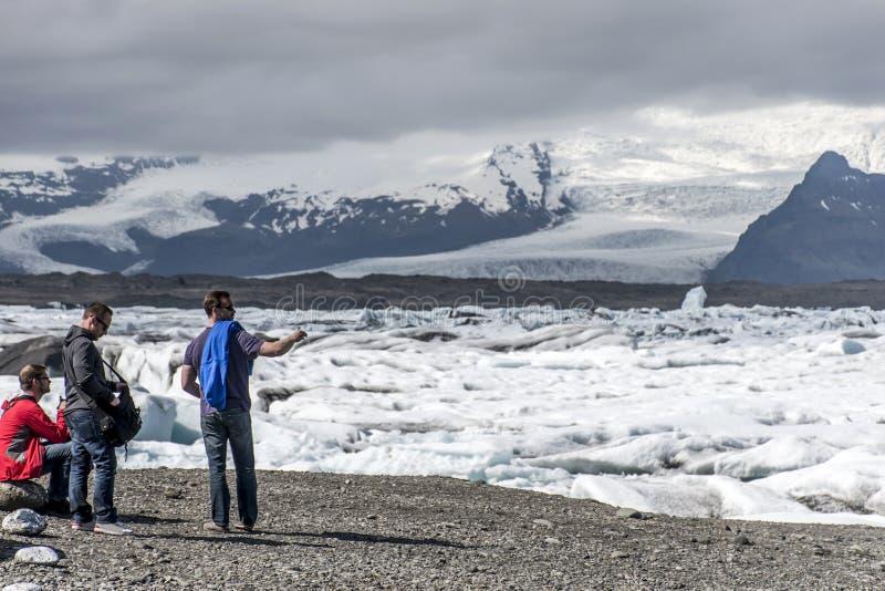 Gli uomini dell'Islanda che stanno alla neve glaciale della natura della laguna di Jokulsarlon del lago del ghiacciaio abbellisco immagine stock libera da diritti
