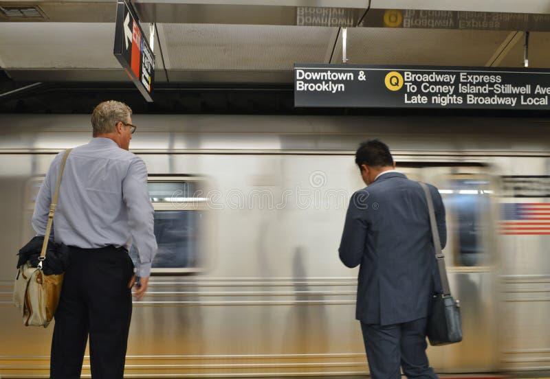 Gli uomini di affari di NYC che aspettano il treno sul lavoro del MTA New York del binario del sottopassaggio permutano immagini stock libere da diritti