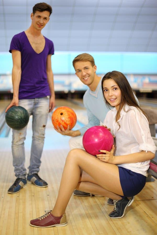 Gli uomini e la ragazza con le sfere nel bowling bastonano; fotografia stock