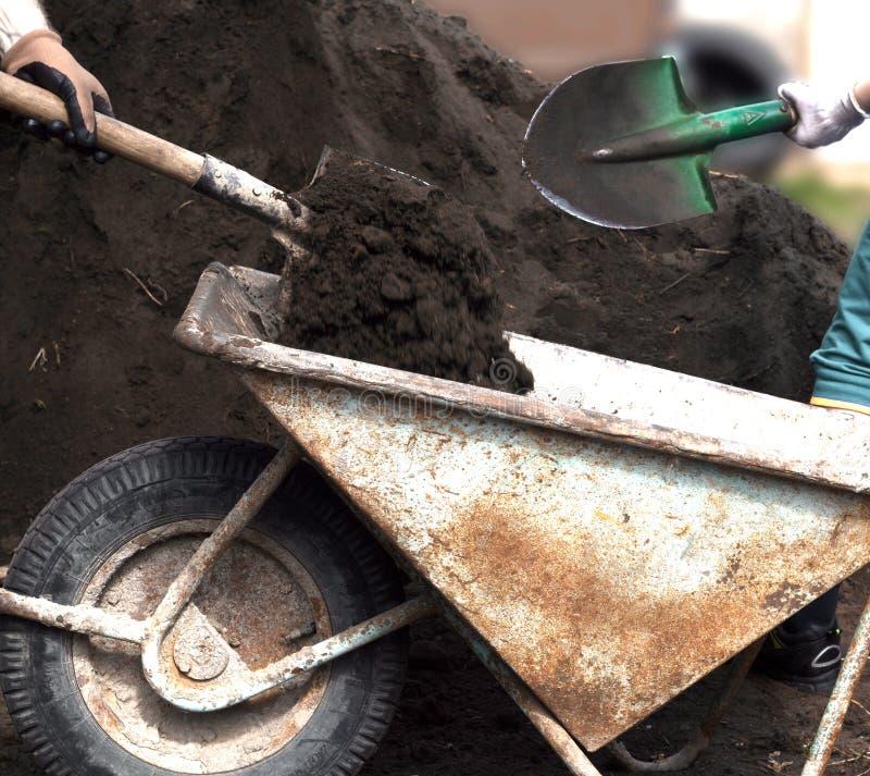 Gli uomini hanno versato il suolo nella carriola con le pale immagini stock