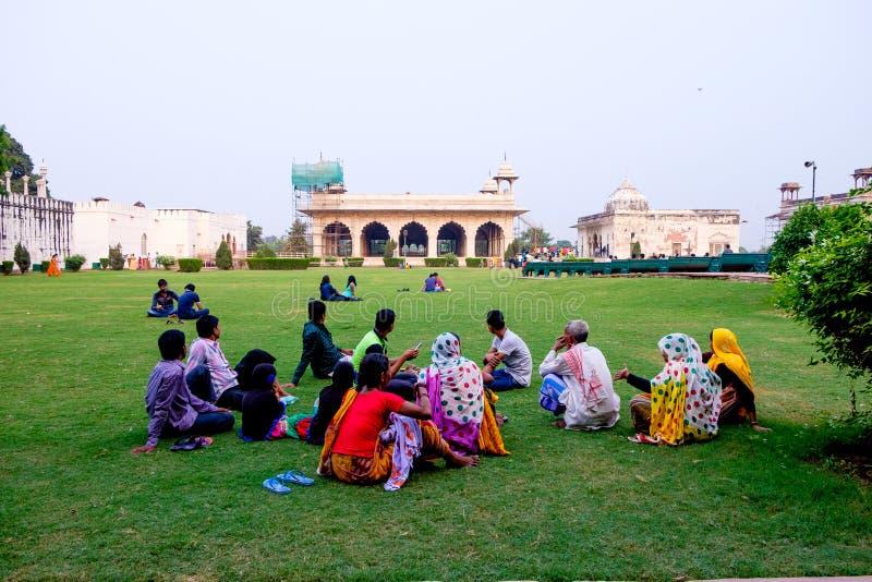 Gli uomini indiani e le donne che si siedono sul gat del raj fanno il giardinaggio al tramonto a Delhi fotografia stock