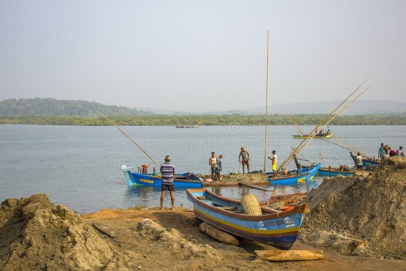 Gli uomini indiani estraggono la sabbia nel modo del fiume barca caricata con la sabbia nell'acqua vicino alla riva fotografia stock libera da diritti