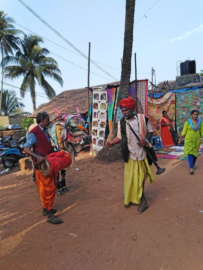 Gli uomini indiani hanno vestito lo stile locale con una mucca Mercato delle pulci di mercoled? Anjuna L'India, Goa fotografie stock libere da diritti