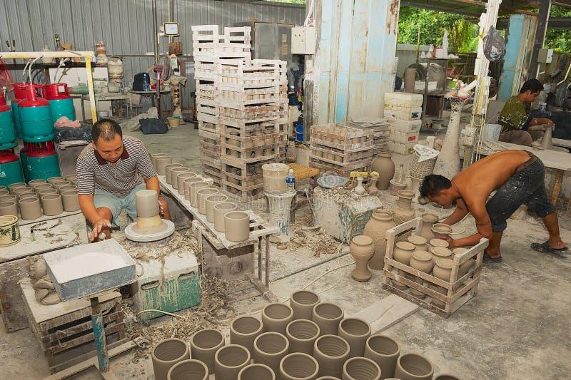 Gli uomini lavorano con caolino per produzione tradizionale dei ricordi in un'officina in Kuching, Malesia fotografie stock libere da diritti