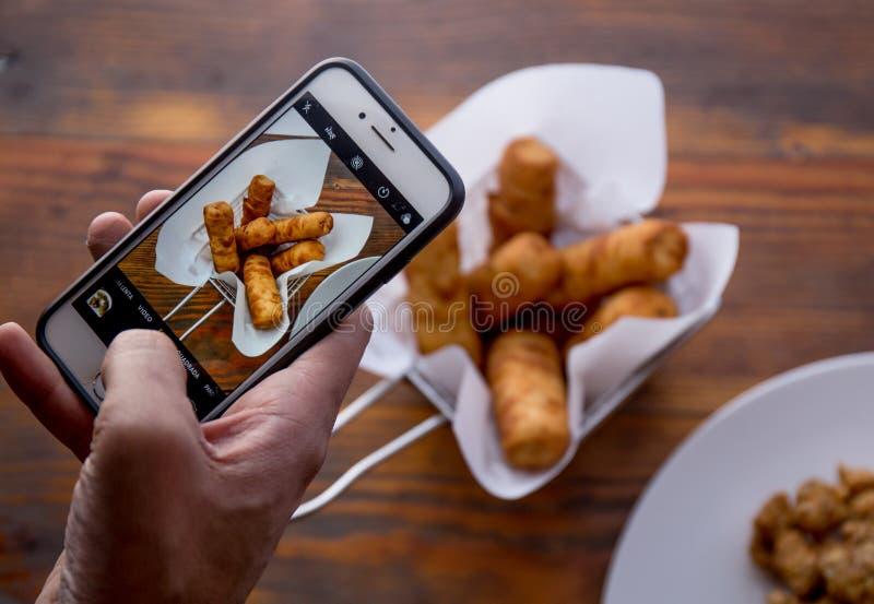 Gli uomini passa la presa della foto dell'alimento di TEQUENOS VENEZUELANO dal telefono cellulare fotografia stock