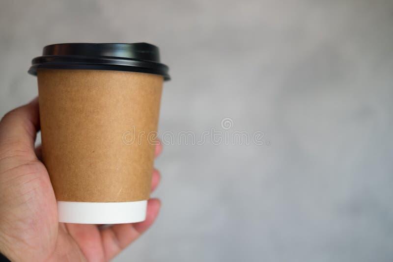 Gli uomini passano dà una tazza di caffè di carta per portare via immagine stock libera da diritti
