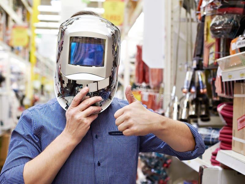 Gli uomini scelgono il saldatore della maschera protettiva in costruzione e strumento del deposito immagini stock libere da diritti
